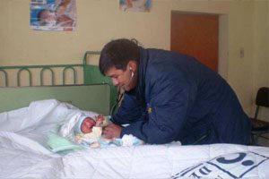 A smiling male doctor, wearing a stethoscope and blue jacket, tends to a new born baby crying on a bed.
