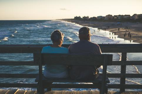 Two older people watching the sunset from a bench