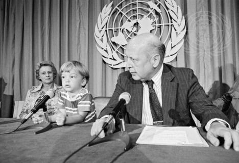 Person with children in front of the UN logo in black and white