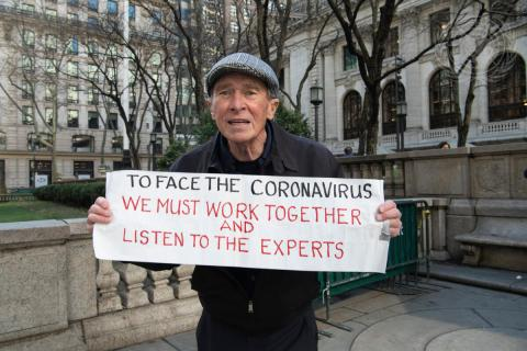 Person holding a sign that encourages society to listen to the COVID-19 experts