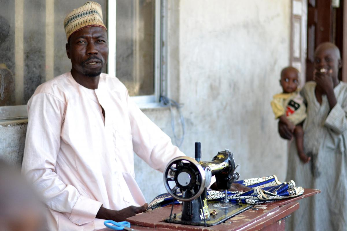 Nigeria: Habacha Kawu, a tailor, standing with his sewing machine.