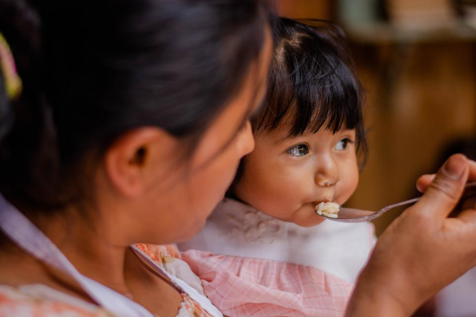 A Guatemalan mother gives her little girl a spoon with rice.