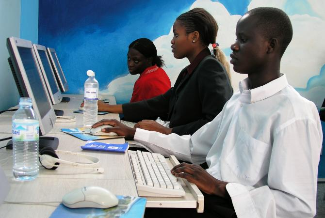 Young communities use computers in an internet cafe in Kampala, Uganda.