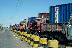 Trucks with cargo containers wait to enter Aden Port