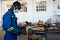 Picture of a factory worker in action at a bed assembling company that supplies hospital in Zimbabwe.