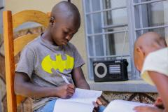 A boy studies at home due to COVID-19, listening to his lessons on the radio every day in Rwanda
