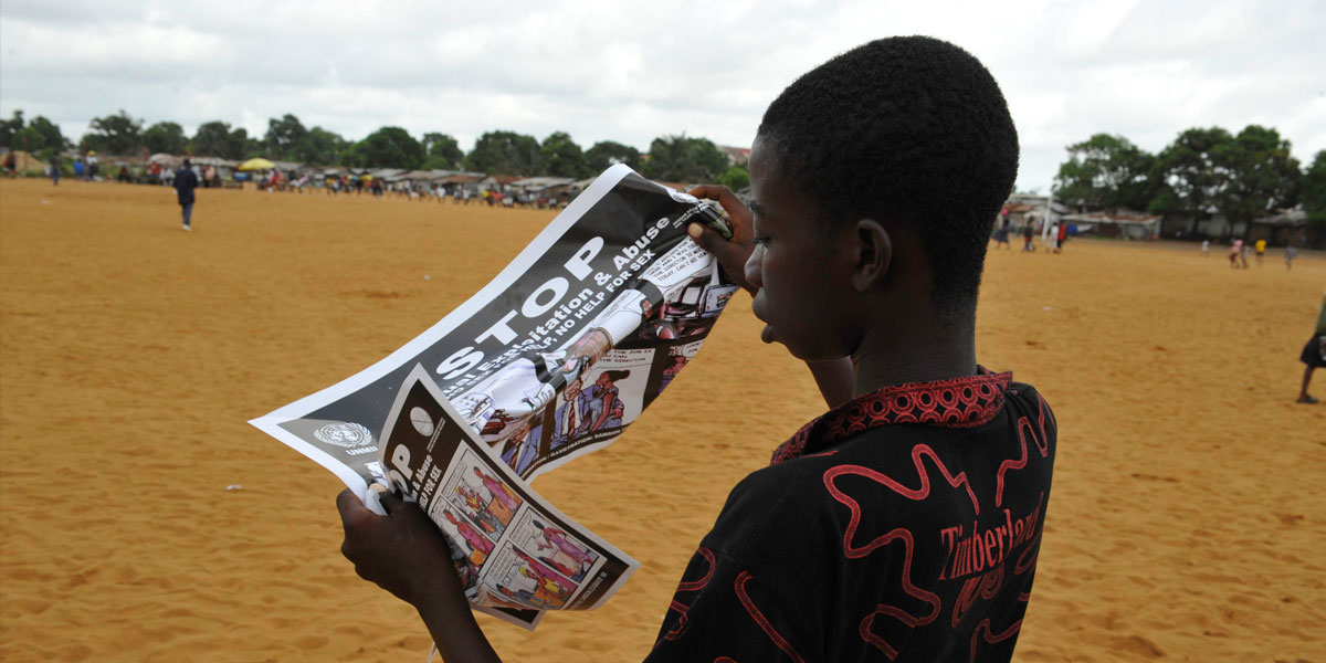 A boy reading a flyer distributed by the UN about Sexual Exploitation and Abuse titled STOP RAPE, part of an awareness campaign in Liberia.