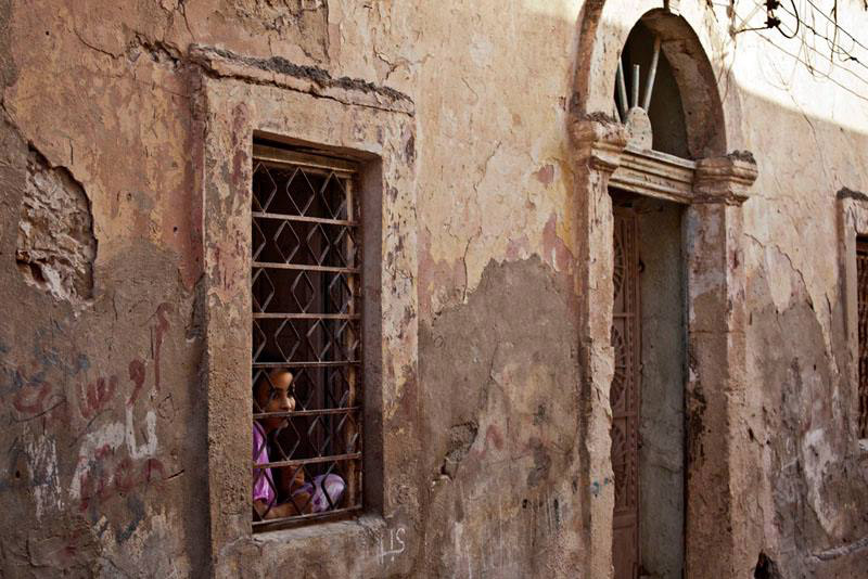 A girl looks out of her house window in Benghazi. Security Council condemned the 'heinous' bomb attacks in Libya.