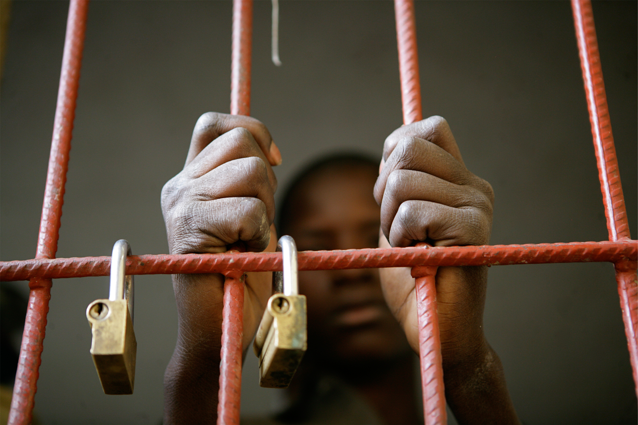 In 2009 in Mali, a 14-year-old boy grips the bars of his cell at the juvenile prison in the town of Mopti, Mopti Region. UNICEF supports a juvenile justice programme and local NGOs that provide education and family reunification services in Mopti.