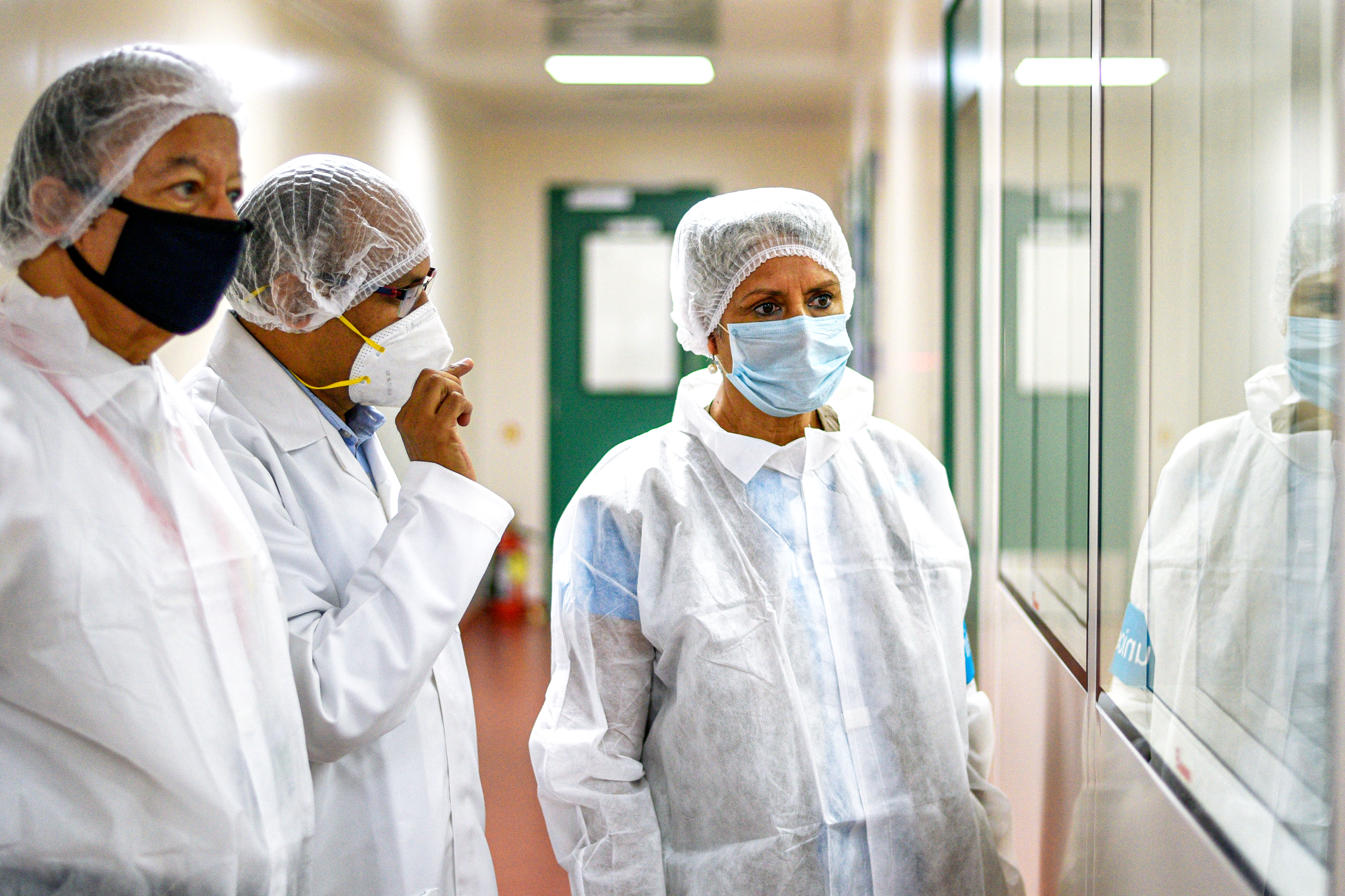 Yasmin wears protective gear as she and colleagues look through a window inside a vaccine facility.