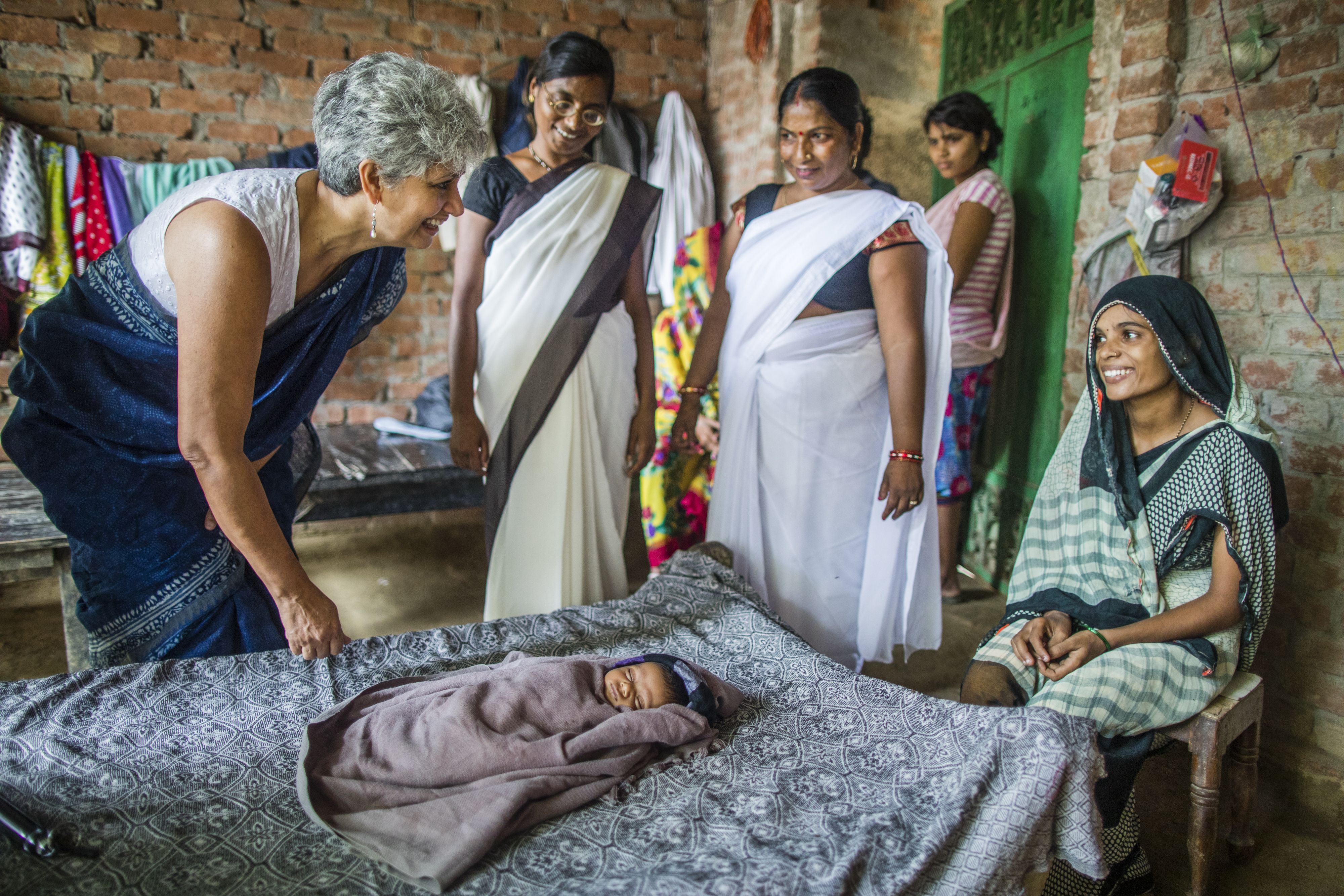 Yasmin is standing next to a bed where a baby is lying down with the mother sitting close by. Two women are standing next to them.