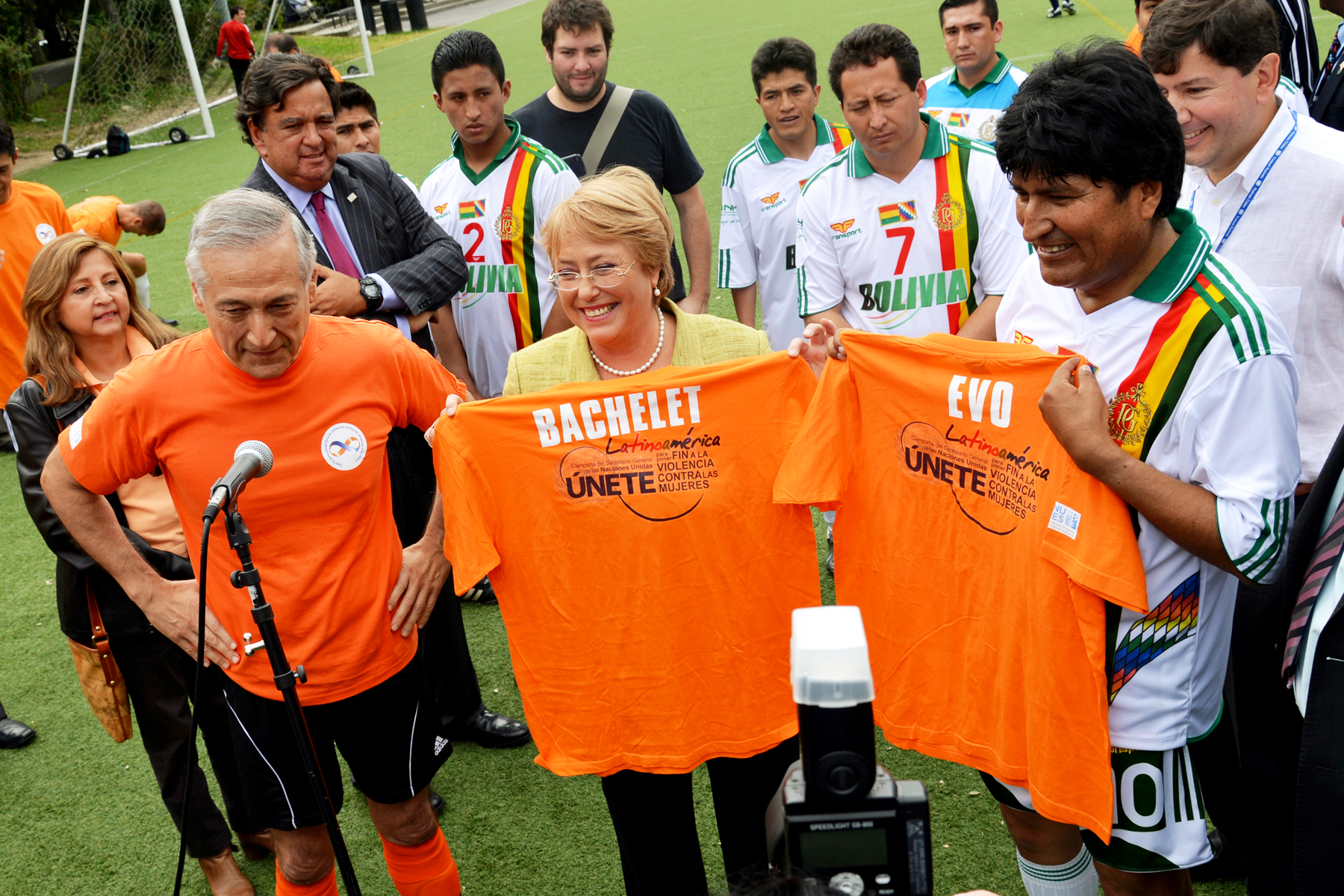 Michelle Bachelet, along with other dignitaries, are standing in a soccer field, proudly holding up orange t-shirts advocating to end all forms of violence against women and girls.