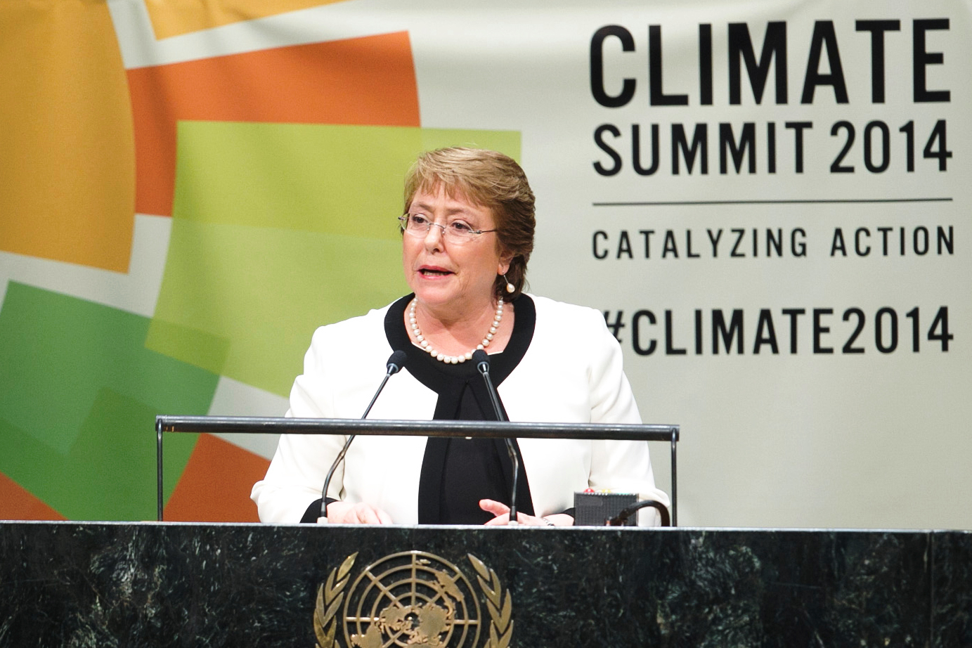 Michelle Bachelet is at a podium delivering a speech at the Climate Summit of 2014.