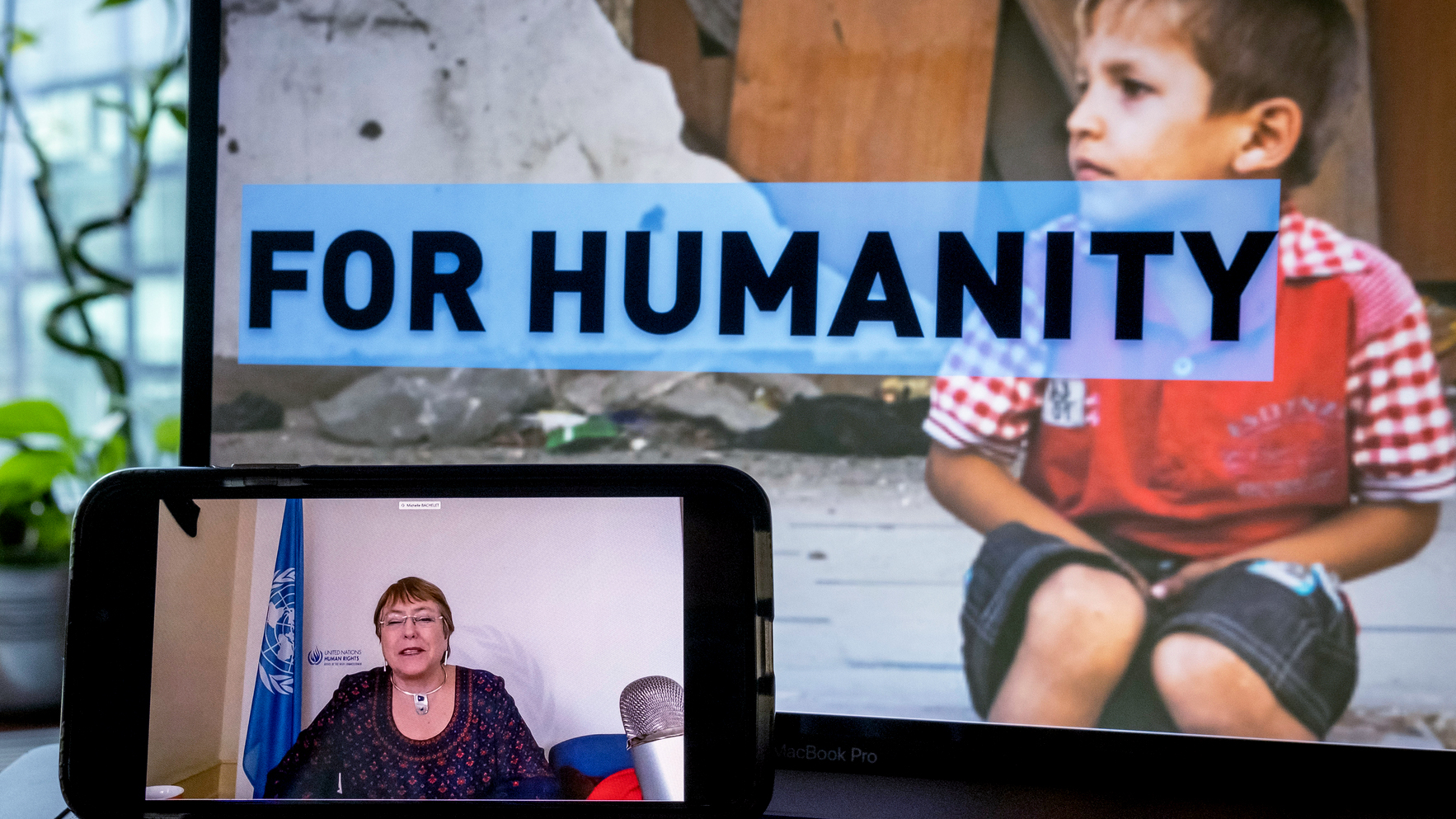 Bachelet is seen on a screen of a smart phone with a laptop behind showing a boy and text reading 'For Humanity'
