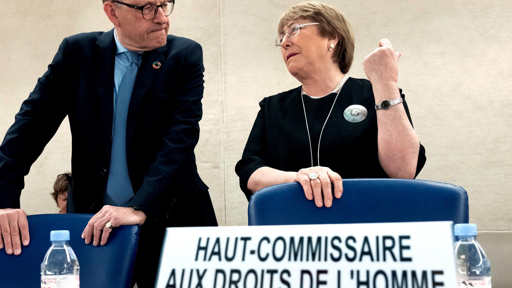 Michelle Bachelet speaking with Michael Møller at a head table in a conference hall.