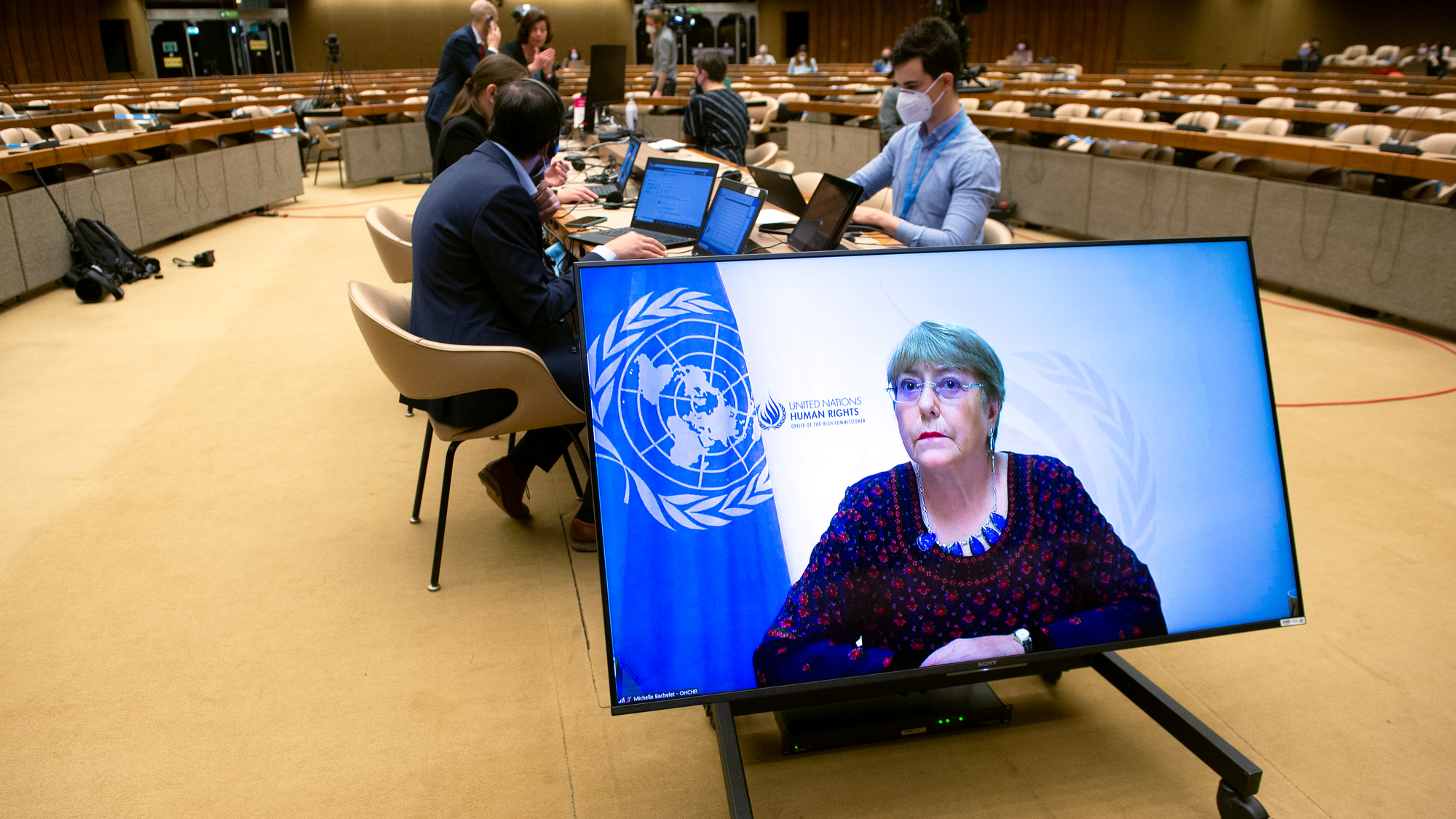 Michelle Bachelet's image is seen on a large screen inside a conference hall