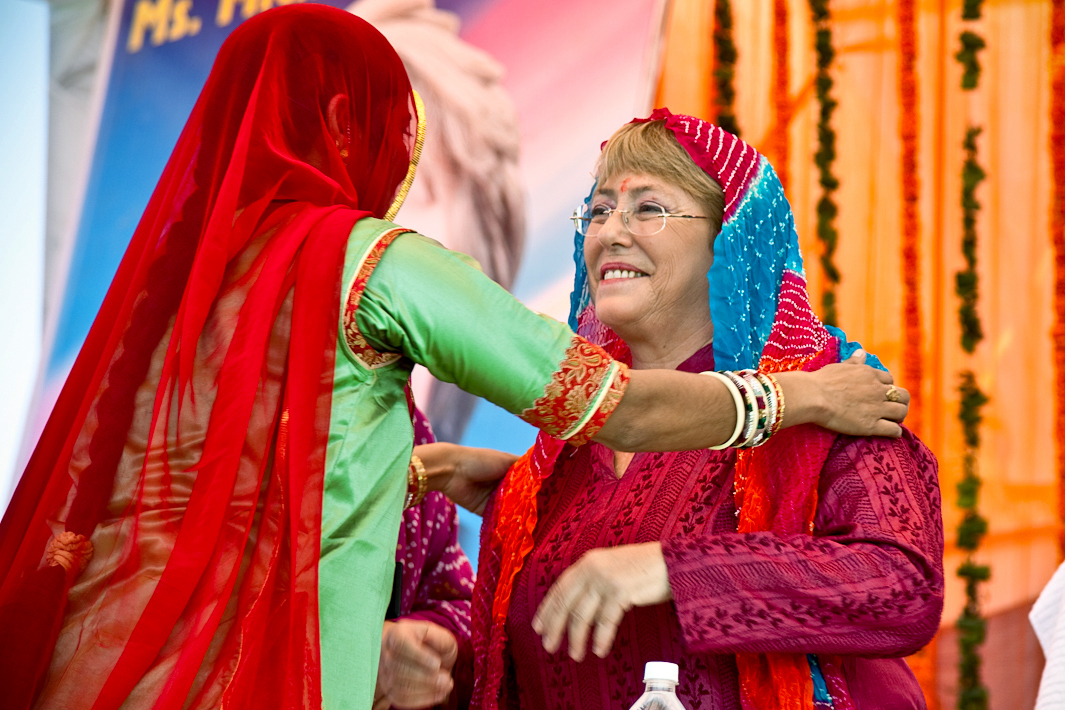 Michelle Bachelet is dressed in Indian attire and is greeted by another woman.