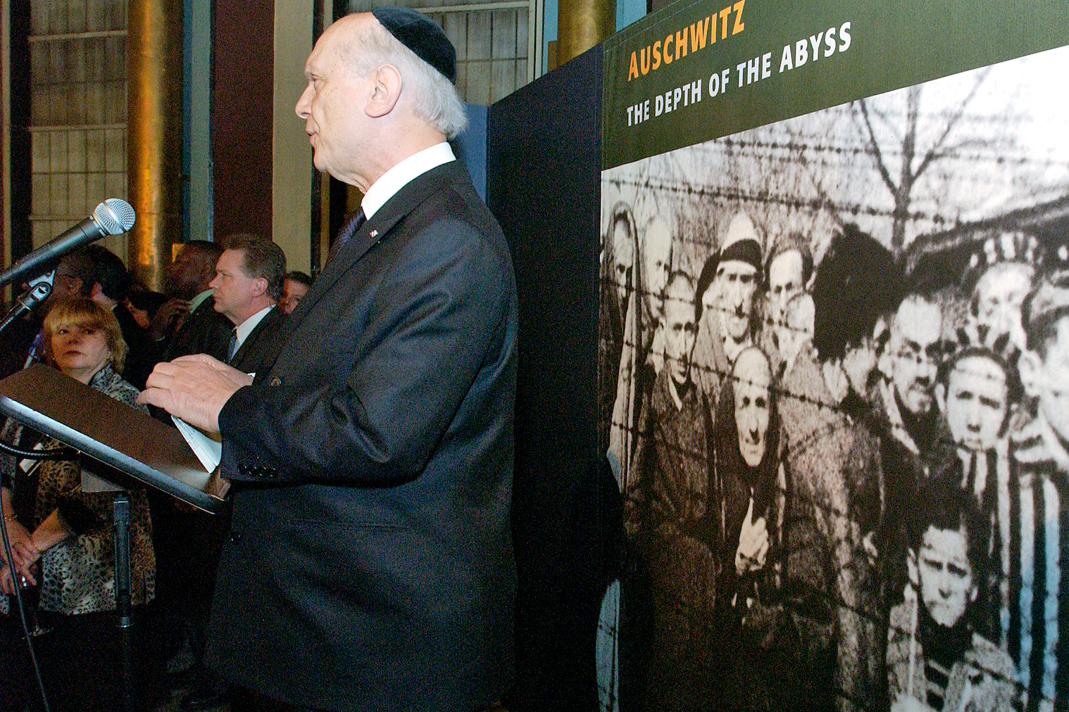 Rabbi Arthur Schneier is at a podium with a large poster depicting 'Auschwitz - the Depth of the Abyss' behind him.