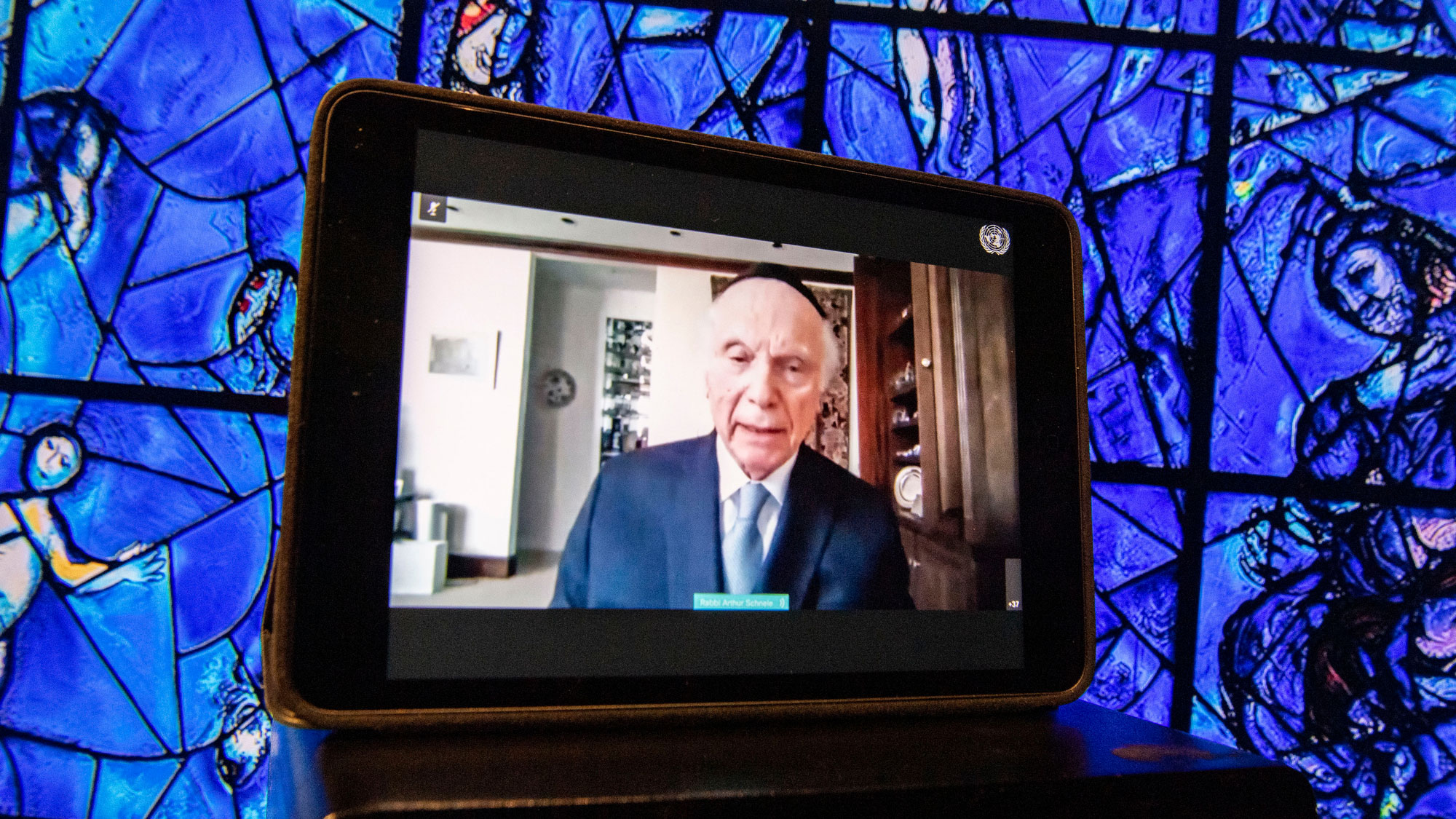 A tablet, with Rabbi Arthur Schneier on view, is leaning against Marc Chagall's colorful stained glass window at UNHQ.