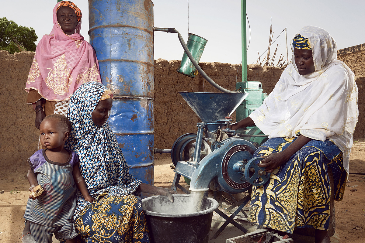 A group of women by a food processing tool.
