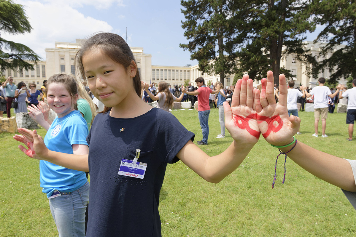 Children put their palms together showing the links painted on them as they form a circle.
