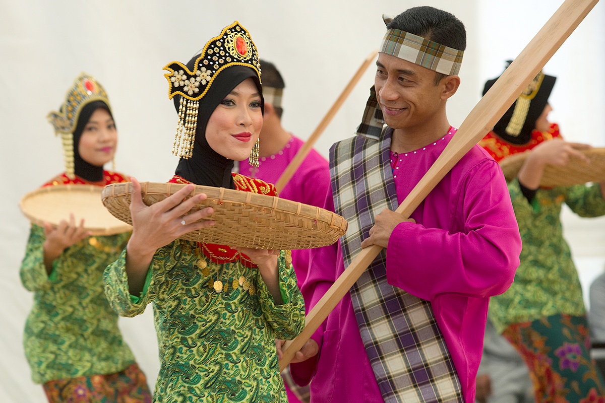 Women and men in traditional dress perform a traditional dance