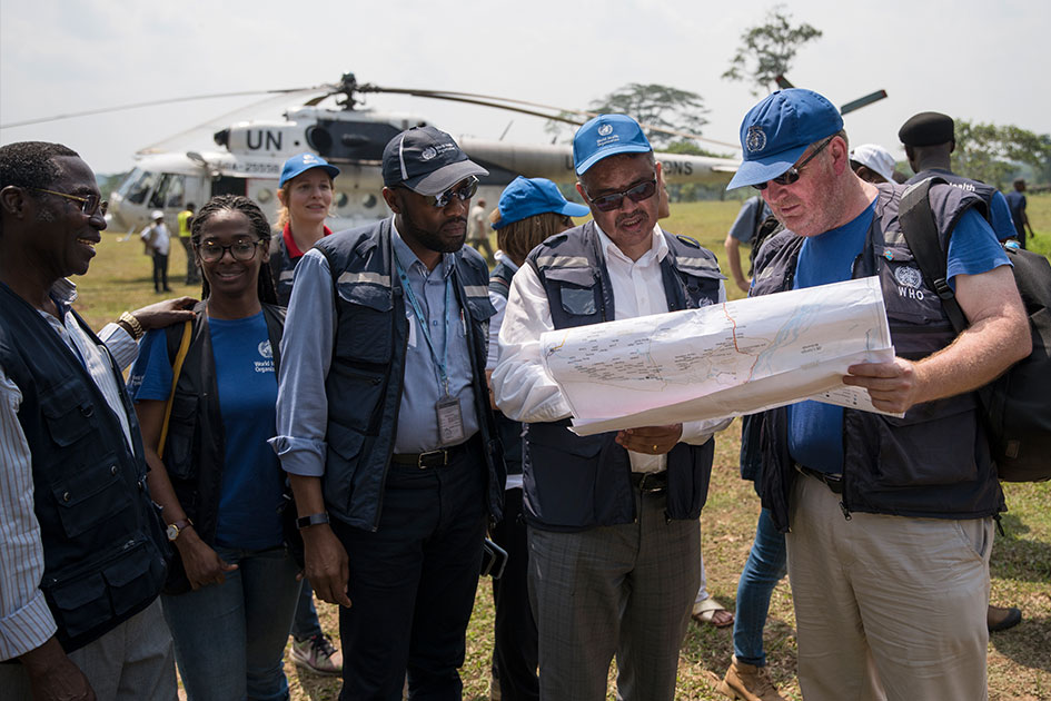 Dr. Ryan and Dr. Ghebreyesus are looking at a map. They are surrounded by their team. A helicopter is seen in the background.