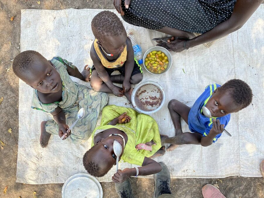 A group of kids sit on a matt eating and looking up at the camera.