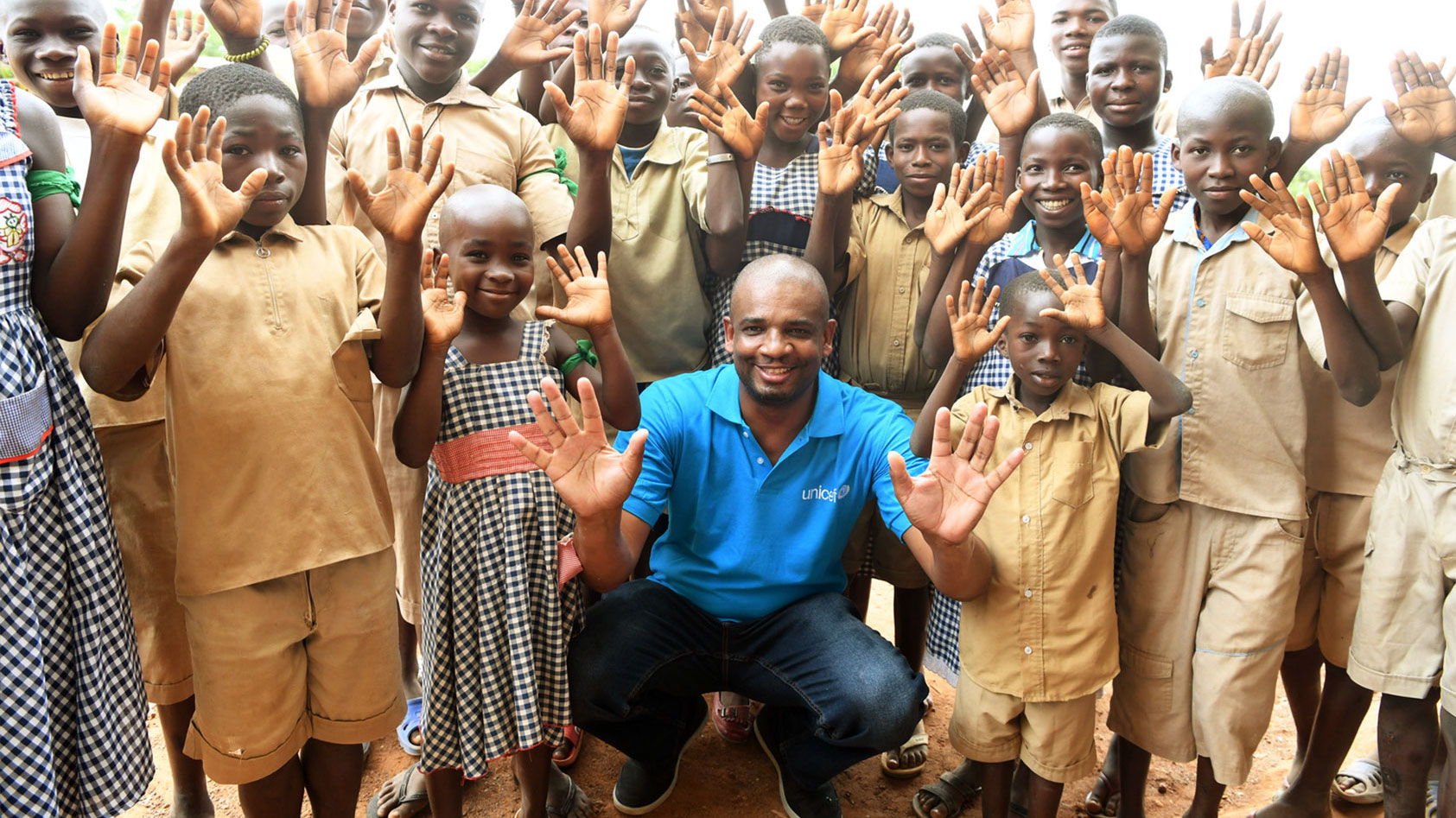 Aboubacar is crouching amidst a group of children. All are holding their hands up.