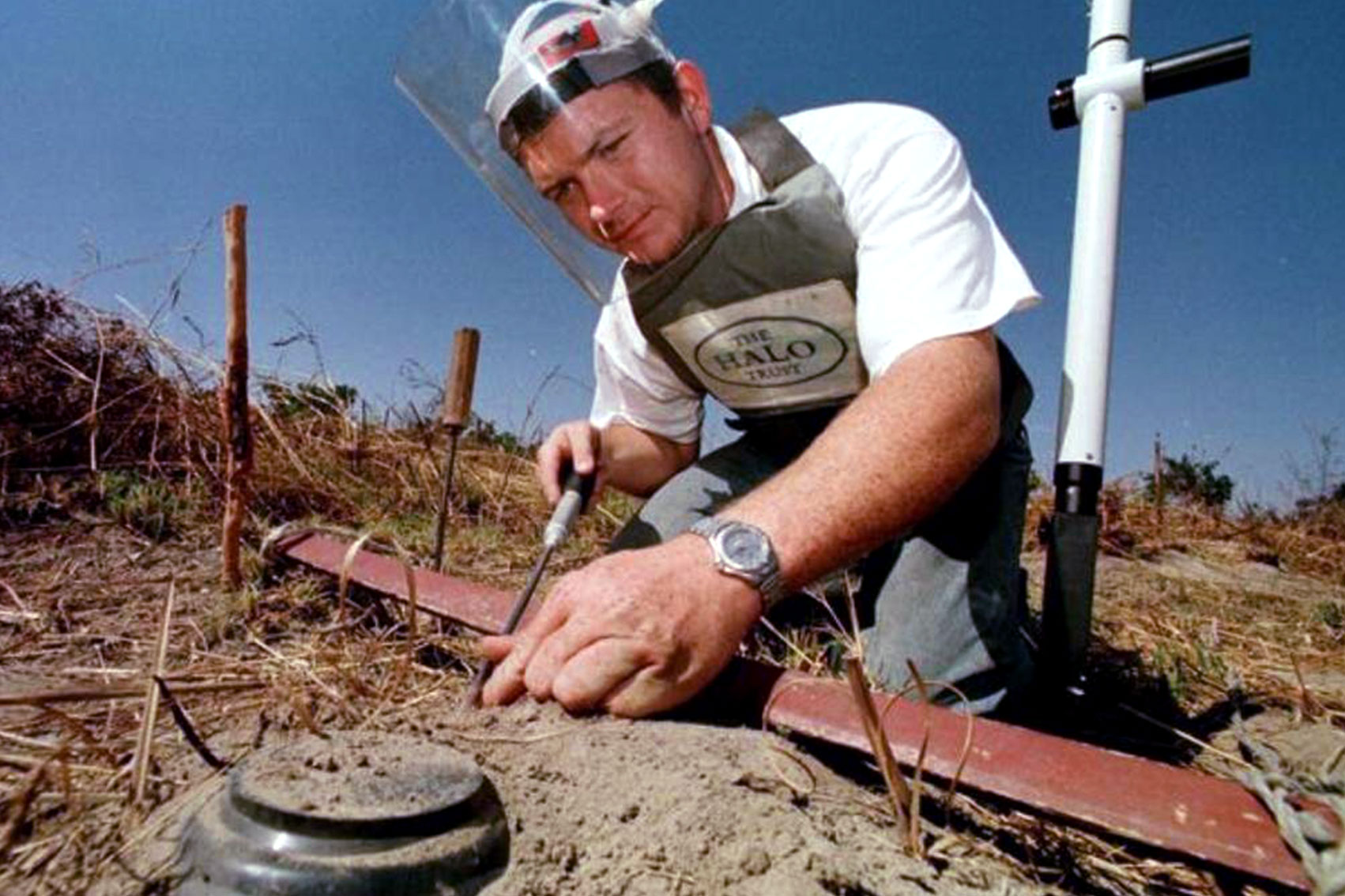 Paul Heslop is on his knees working on deactivating a mine.