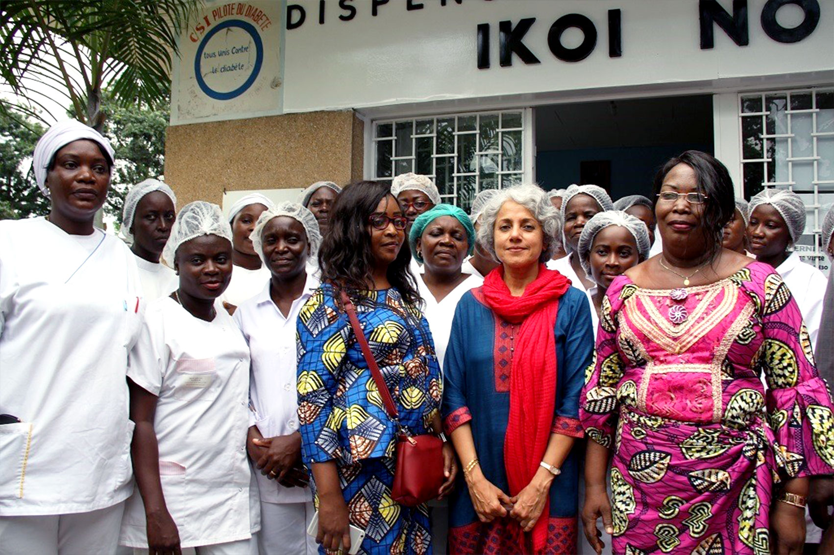 Dr. Soumya stands for a photo op surrounded by health workers