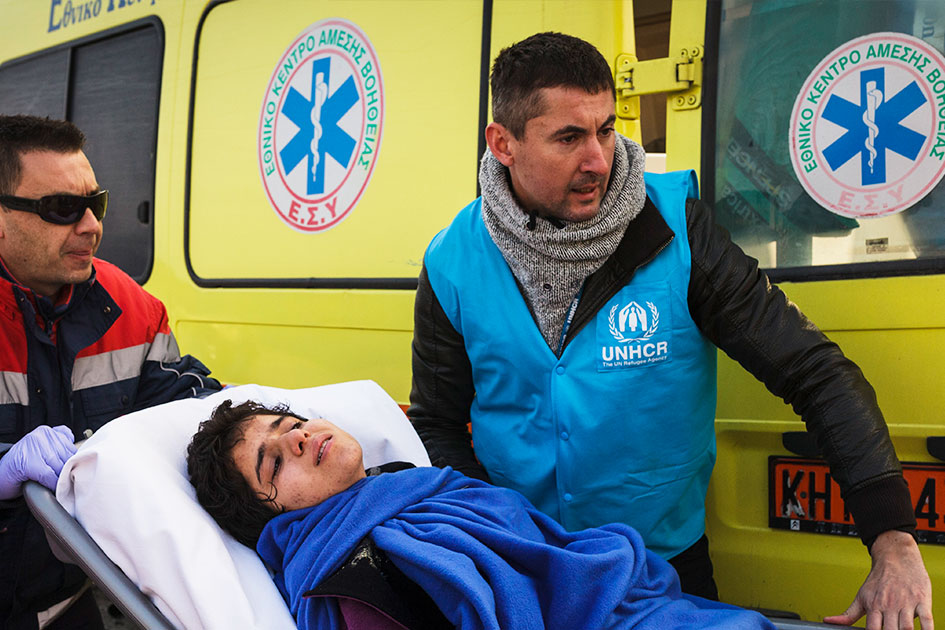 Boris Cheshirkov carrying a refugee child on a stretcher with the help of another person.
