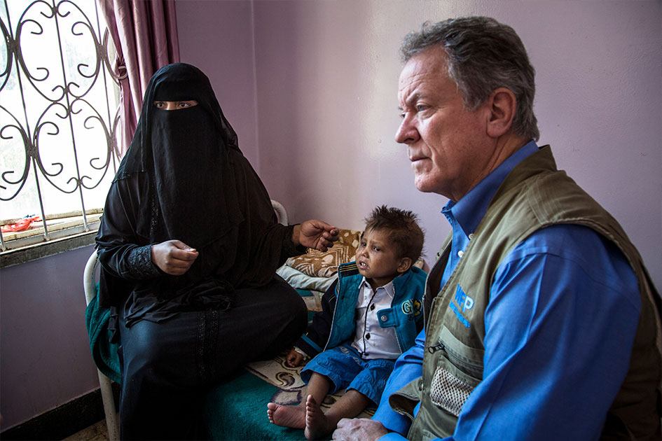 David Beasley sits next to a child and mother on a hospital bed in Yemen.