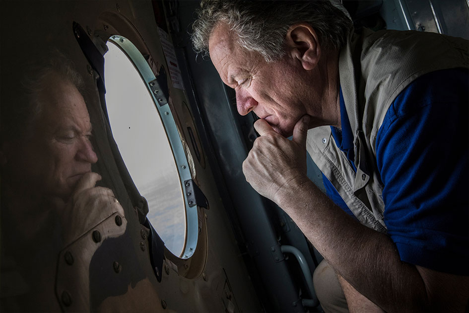 David Beasley looks out through a window in an airplane.