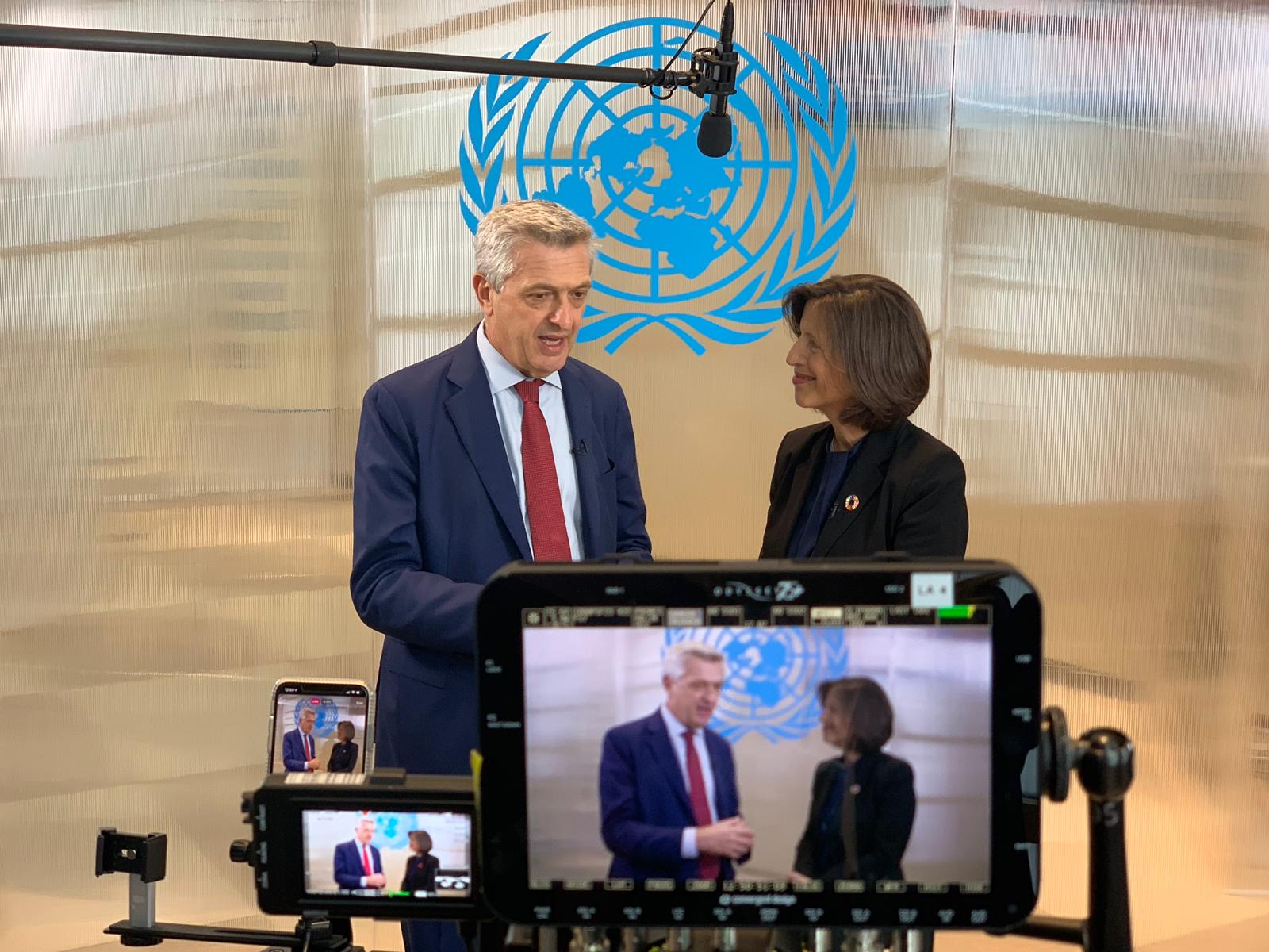 Cameras record a UN official interviewing another.