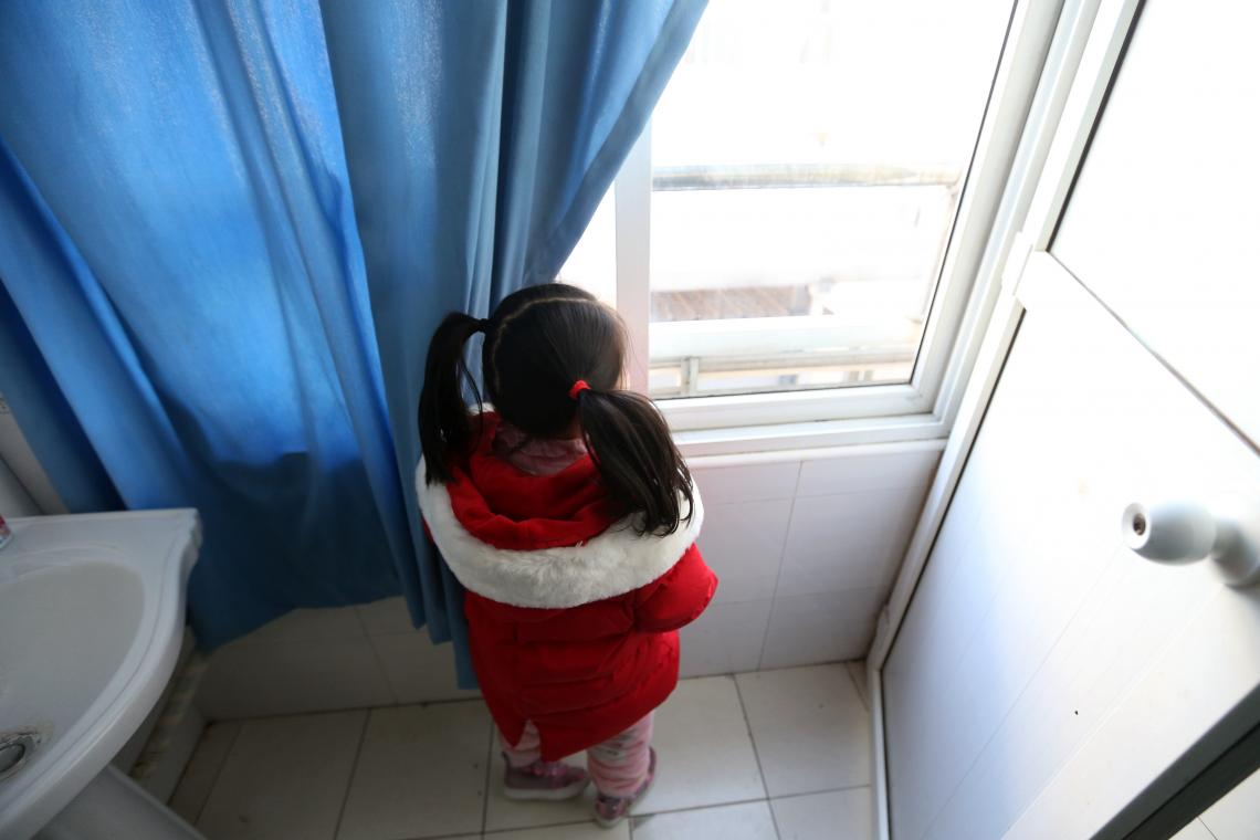 young girl stands by window in bathroom