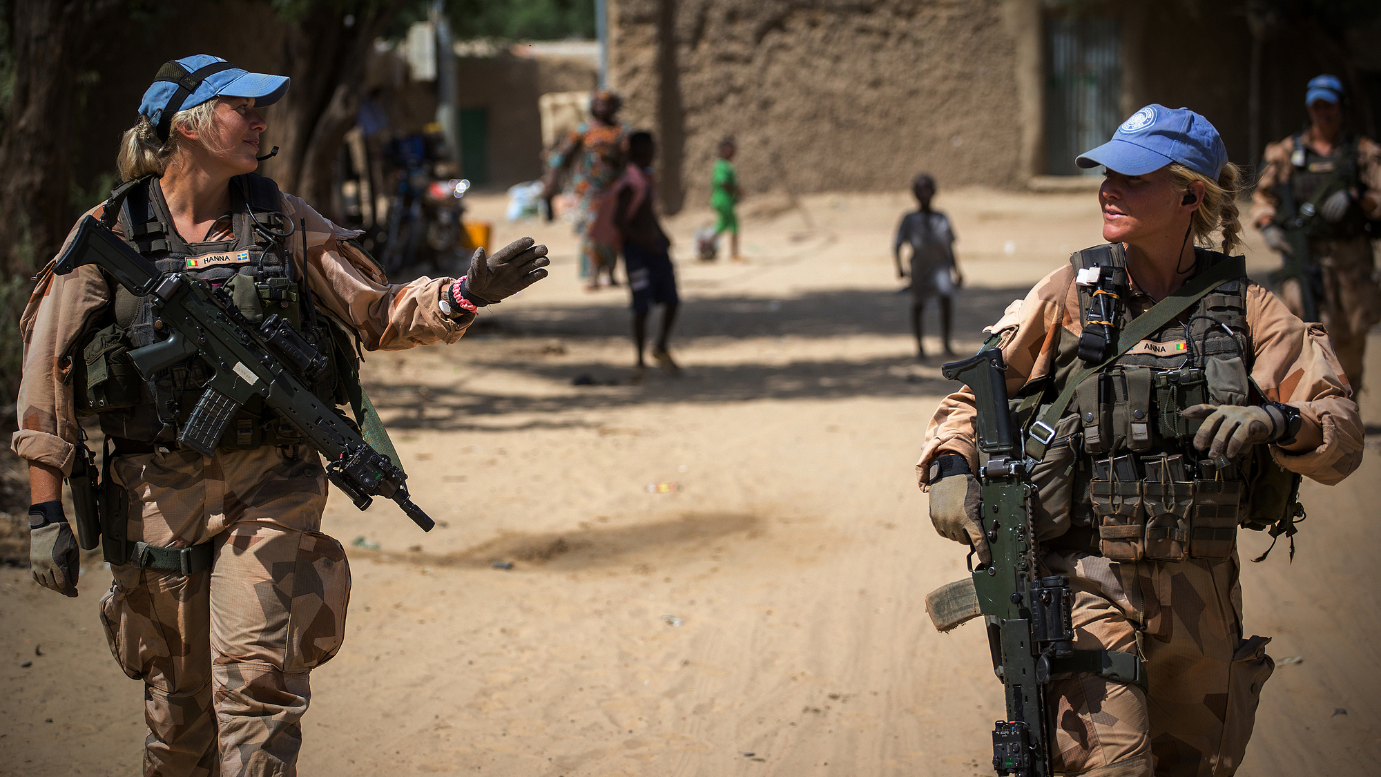 Two female Swedish Marines walk down a street in Mali in 2018 with children in the background.