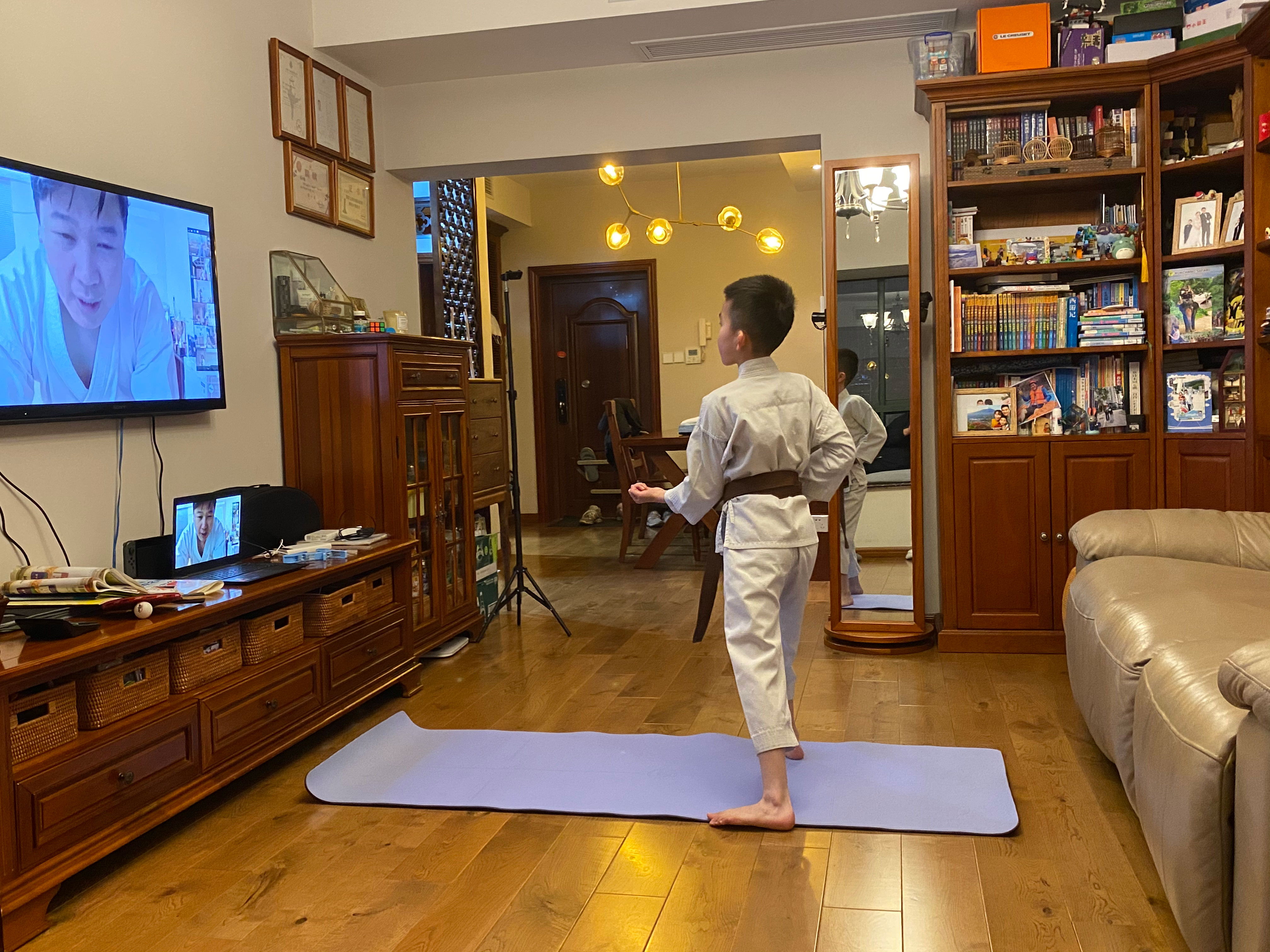 A child doing Karate in front of the TV