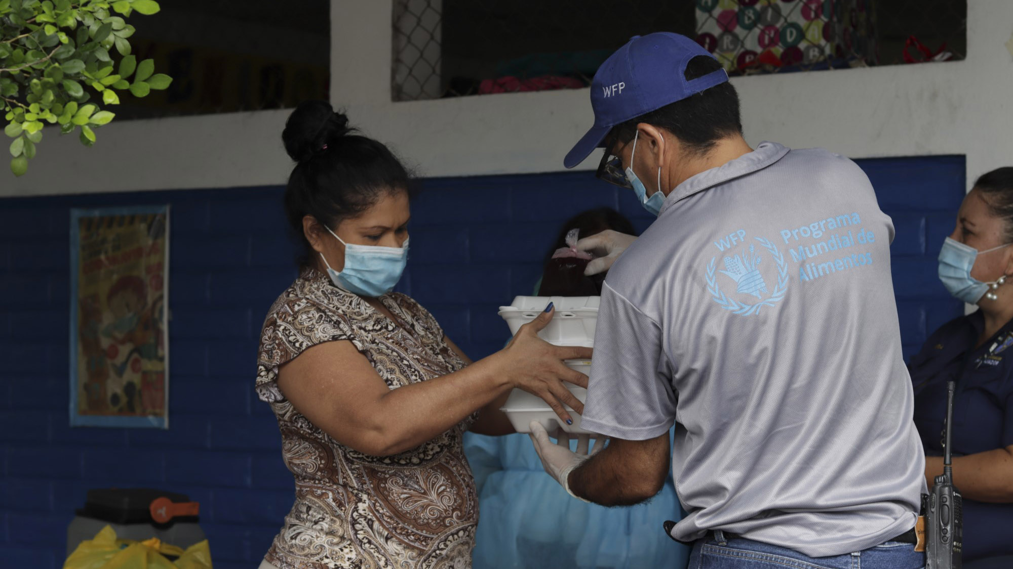A World Food Programme staff member handing food to a woman in El Salvador.