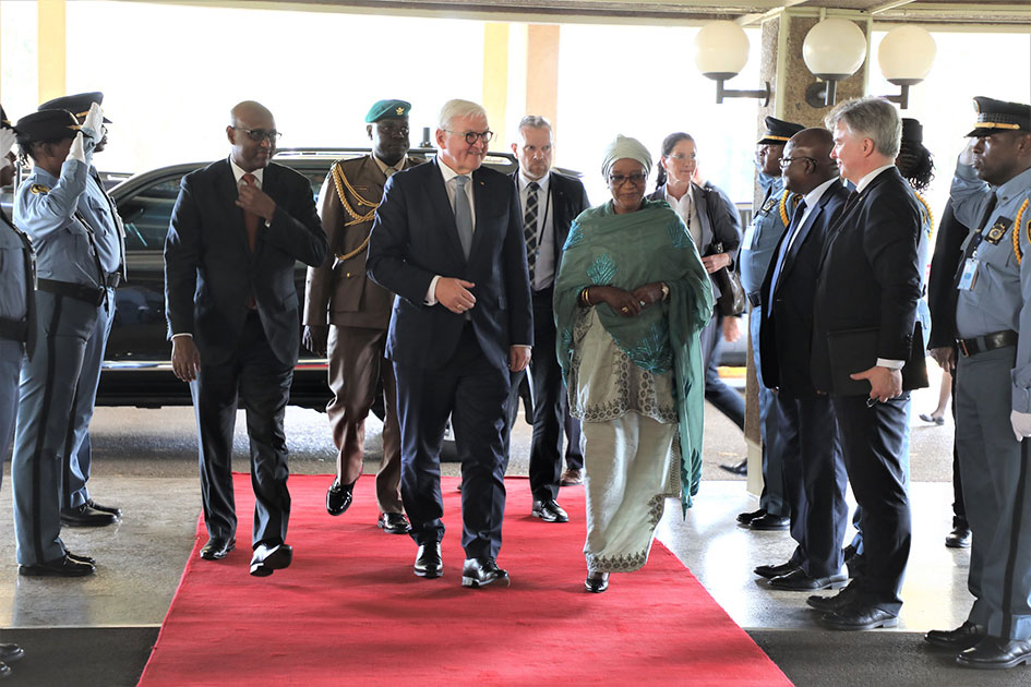 Bangura walks on a red carpet with the German President.