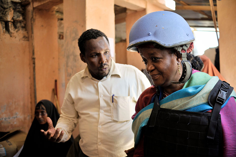 A man speaks to Ms. Bangura. She is wearing a blue helmet and protective vest.