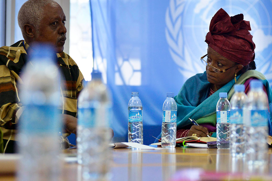 Bangura, seated at a table, is in deep discussion with a member of the Police Advisory Committe.