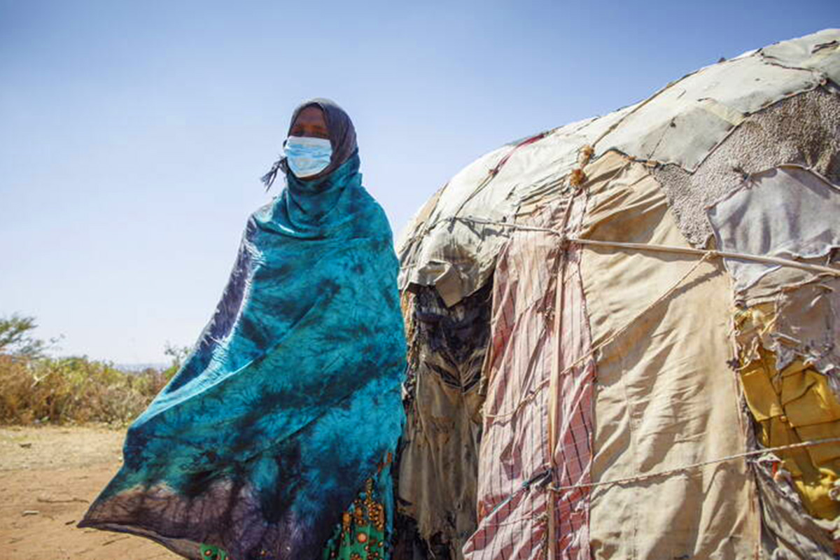 A woman wearing a facemask sits in front of a makeshift shelter.