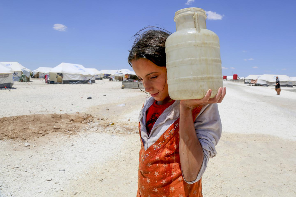 A girl carries a container of water on her shoulder.