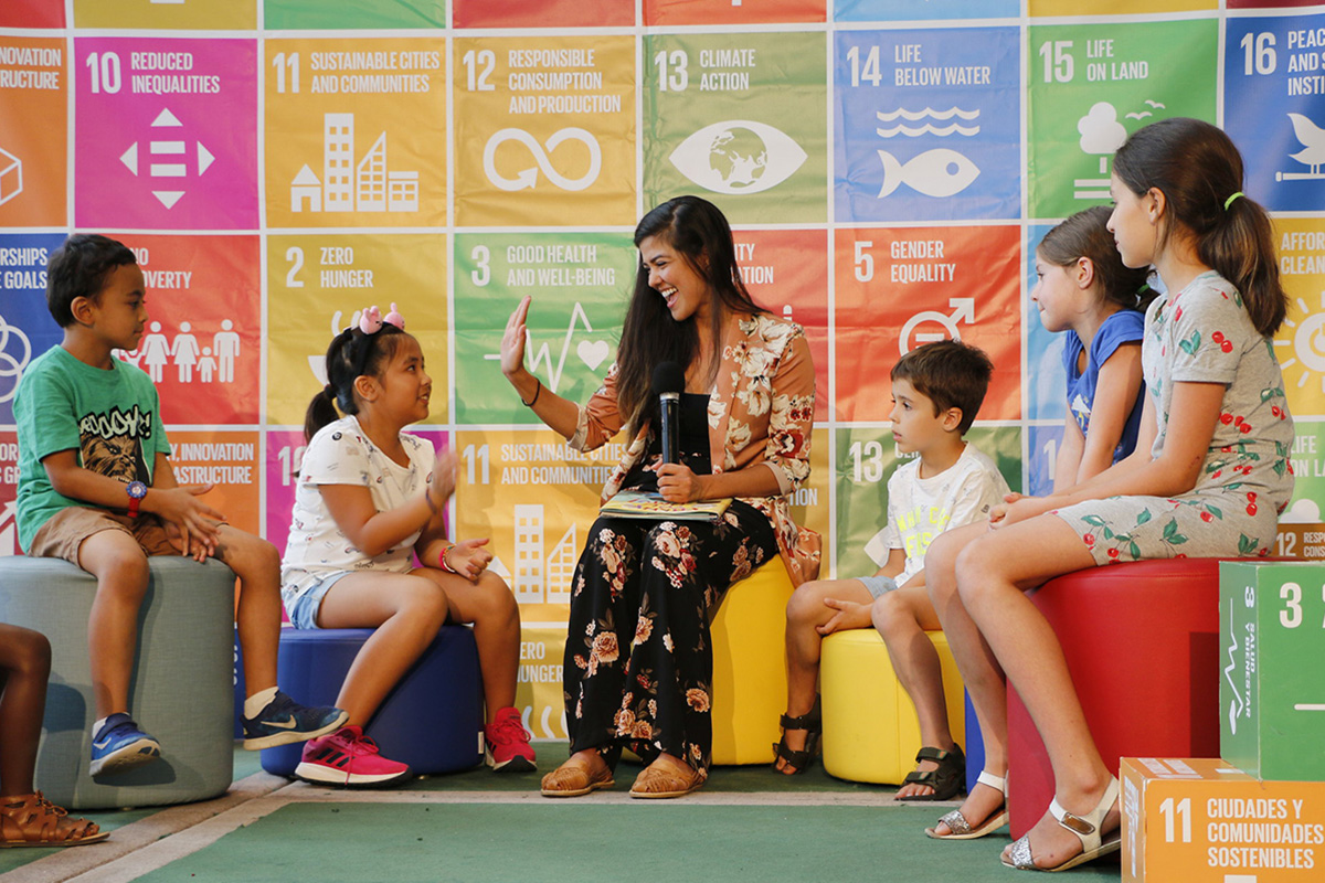 A woman smiling surrounded by kids on a stage where the SDGs logos are displayed as a background
