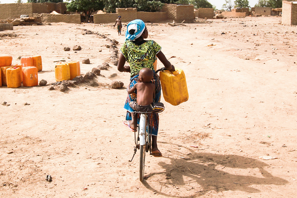 Kids bringing water in containers while riding their bike on a dry land.
