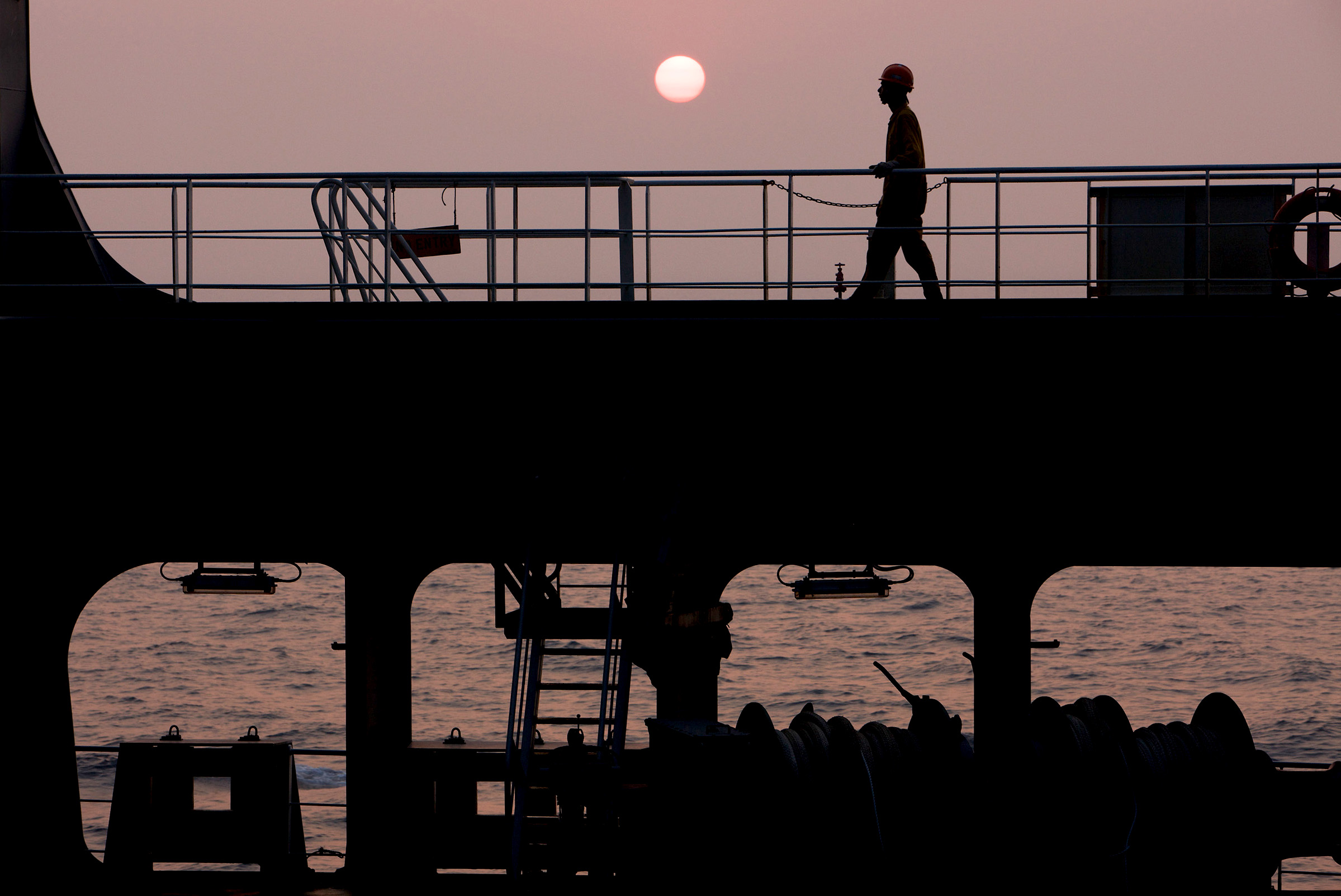 Silhouette of seafarer on a boat against the sunset