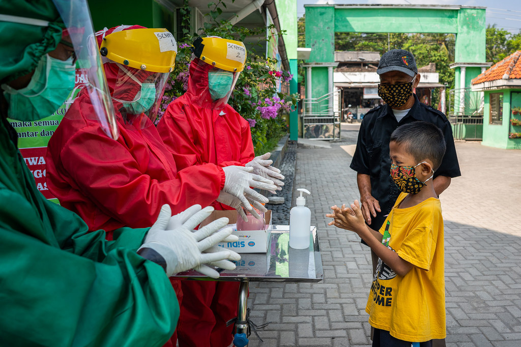 Health workers demonstrate proper handwashing to a child wearing a mask.