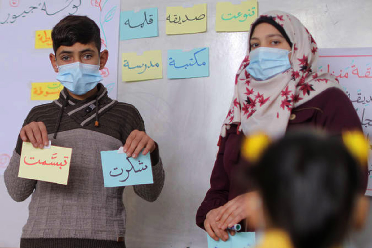 A boy stands next to a girl in a classroom holding up note cards