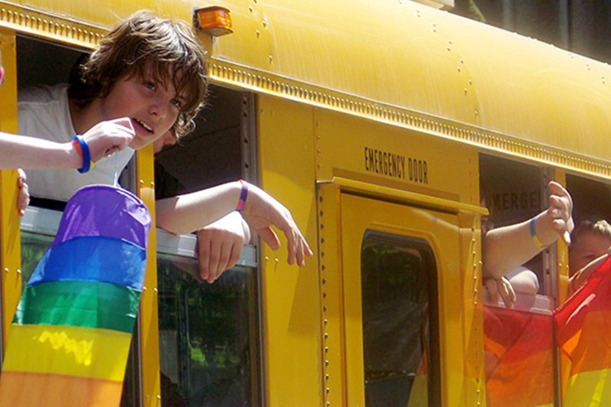 Students hold out rainbow flags from a school bus.